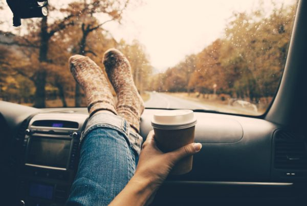 image of legs on a dashboard with a coffee